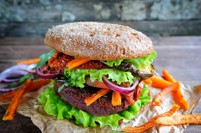 Fresh beetroot lentil vegan burger with baked vegetables and sun-dried tomatoes, selective focus