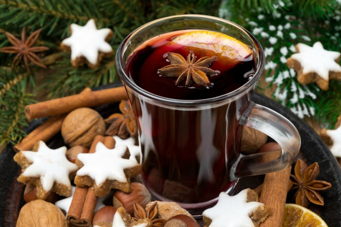 cup of mulled wine, cookies in the shape of stars and spices, close-up