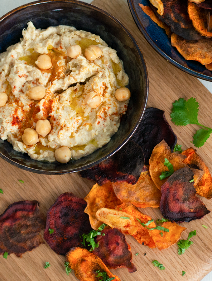 Bowl of homemade hummus served in a ProCook Vaasa bowl next to some vegetable crisps