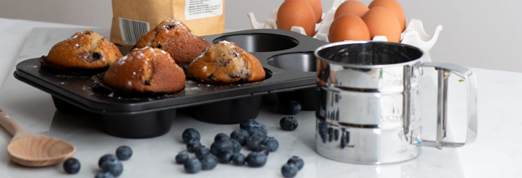 ProCook Muffin Tin and Flour Sifter alongside baked blueberry muffins and a scattering of fresh blueberries