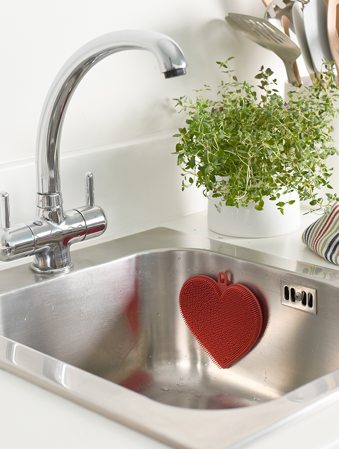 ProCook heart shaped Silicone Scrubber in sink for cleaning dishes
