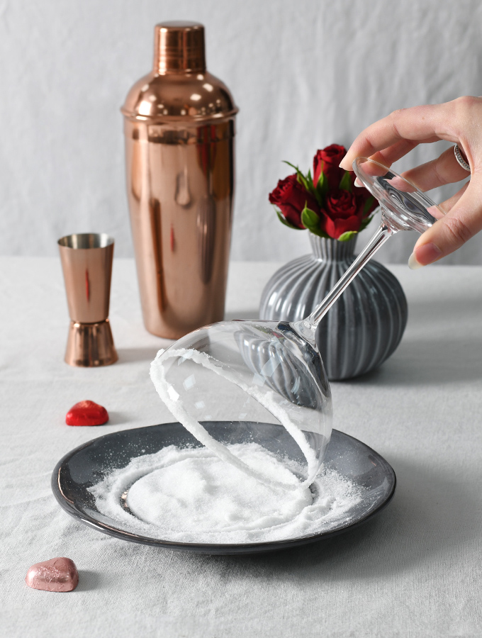 Dipping ProCook Champagne Coupes into sugar to make a Valentine's Love Potion Cocktail
