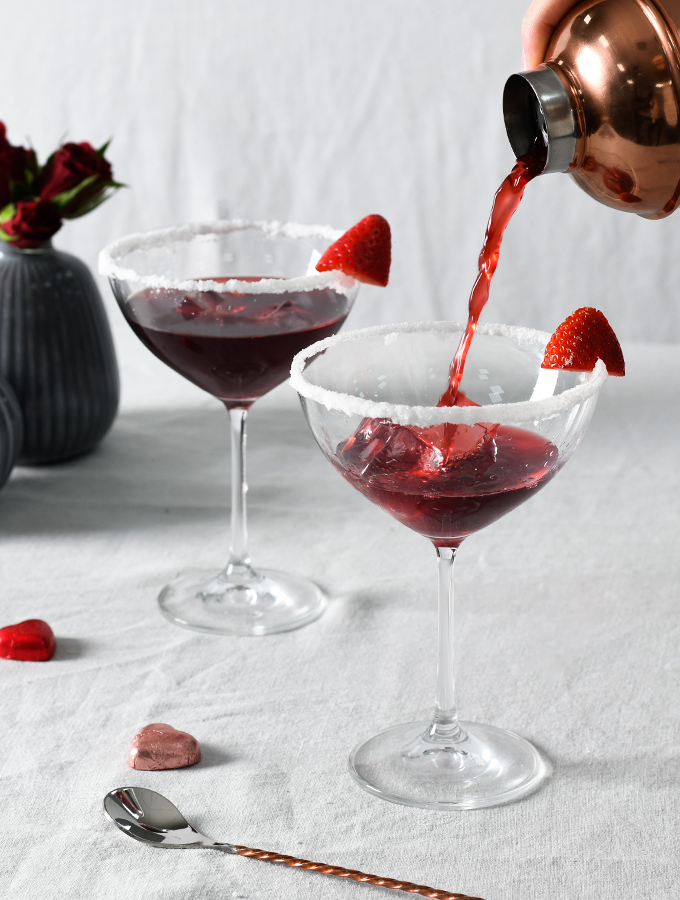 Pouring Valentine's Love Potion cocktail from a ProCook cocktail shaker into champagne coupes